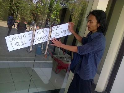 SEGEL DORMITORY: Rizal, mahasiswa pengunjuk rasa yang tergabung dalam KAMPAK (Koalisi Aksi Mahasiswa Pemberantas Korupsi) menempelkan kertas sepanjang 1 meter bertuliskan 'Gedung Ini Kami Segel, Milik Mahasiswa Tak Mampu' di pintu masuk asrama putra. (RMY)